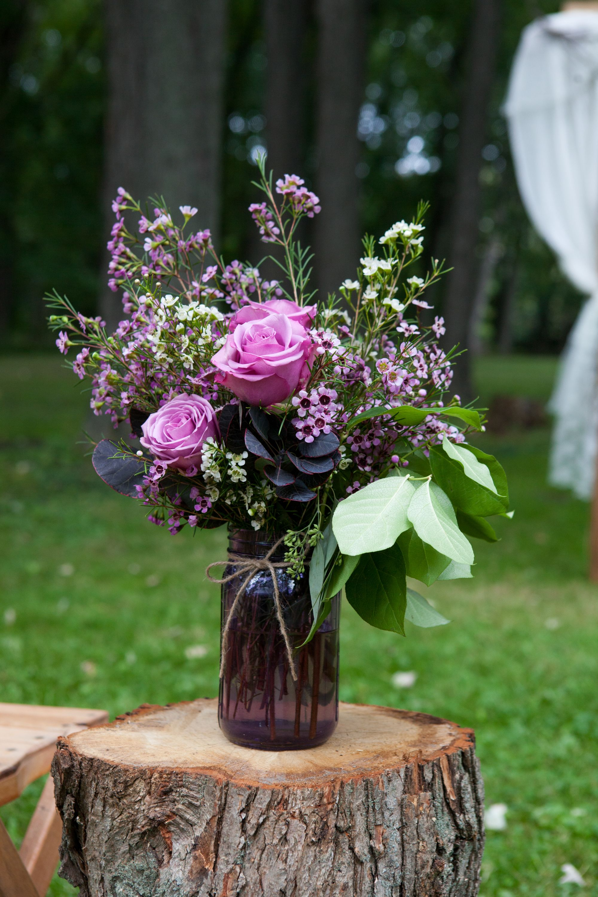 Purple Rose And Wax Flower Mason Jar Decoration On A Round Of