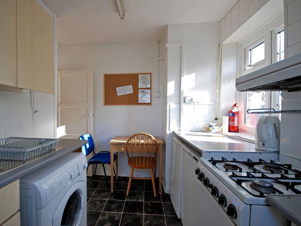 Cucina con lavatrice e tavolo