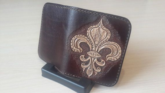 Cardholder is made in minimalism style. It is compact, slim and elegant.  It is to taste of persons who appreciate the simplicity of style and quality.  It is decorated with the sign of the royal dynasties Heraldic lily, and it is also possible to make such cardholder with the monogram of your loved one.  Inside there are compartments for folded banknotes and compartments for credit or business cards.  Size - 10cm. x 8cm. (Folded)  Exclusive products are made of genuine high quality…