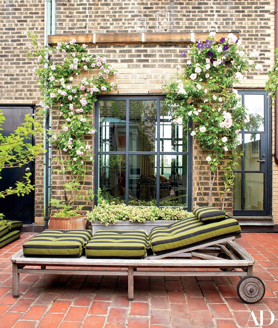Climbing roses flank a window on an upper terrace; a Perennials stripe covers the chaise longue cushions, and the low planter brims with ornamental oregano.