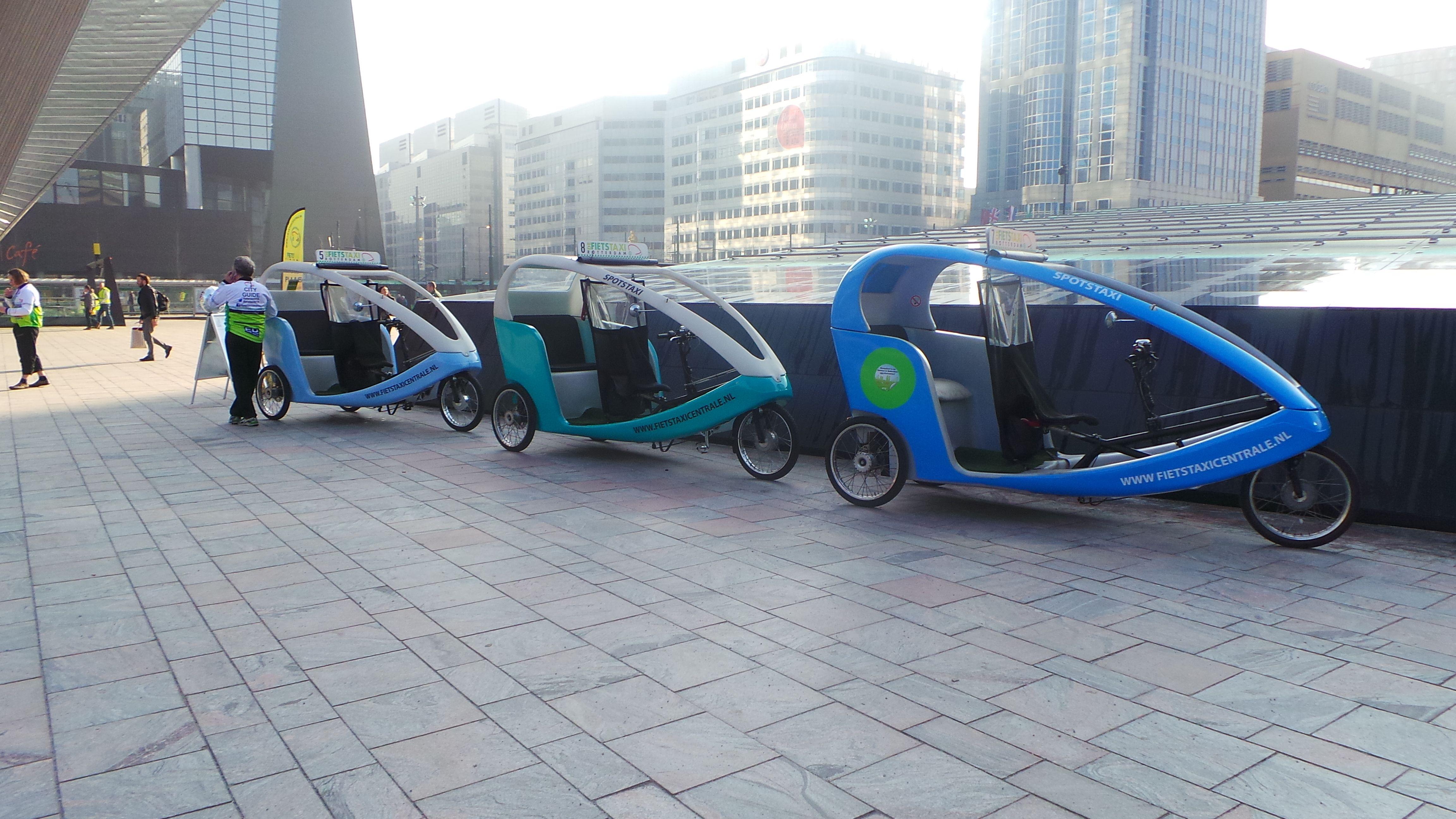 Dit zijn fietstaxi's op het nieuwe Centraal Station Rotterdam en dit is hun officiële standplaats. Maak een gezellig tour door Rotterdam met deze leuke taxi's!