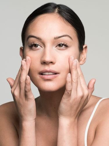 """Step 1: Rub two drops of foundation between your hands, """"then swipe your fingers on the apples of your cheeks, sides of your nose, and across your forehead and chin,"""" says Roncal. """"Finger-pat to blend everything in."""""""