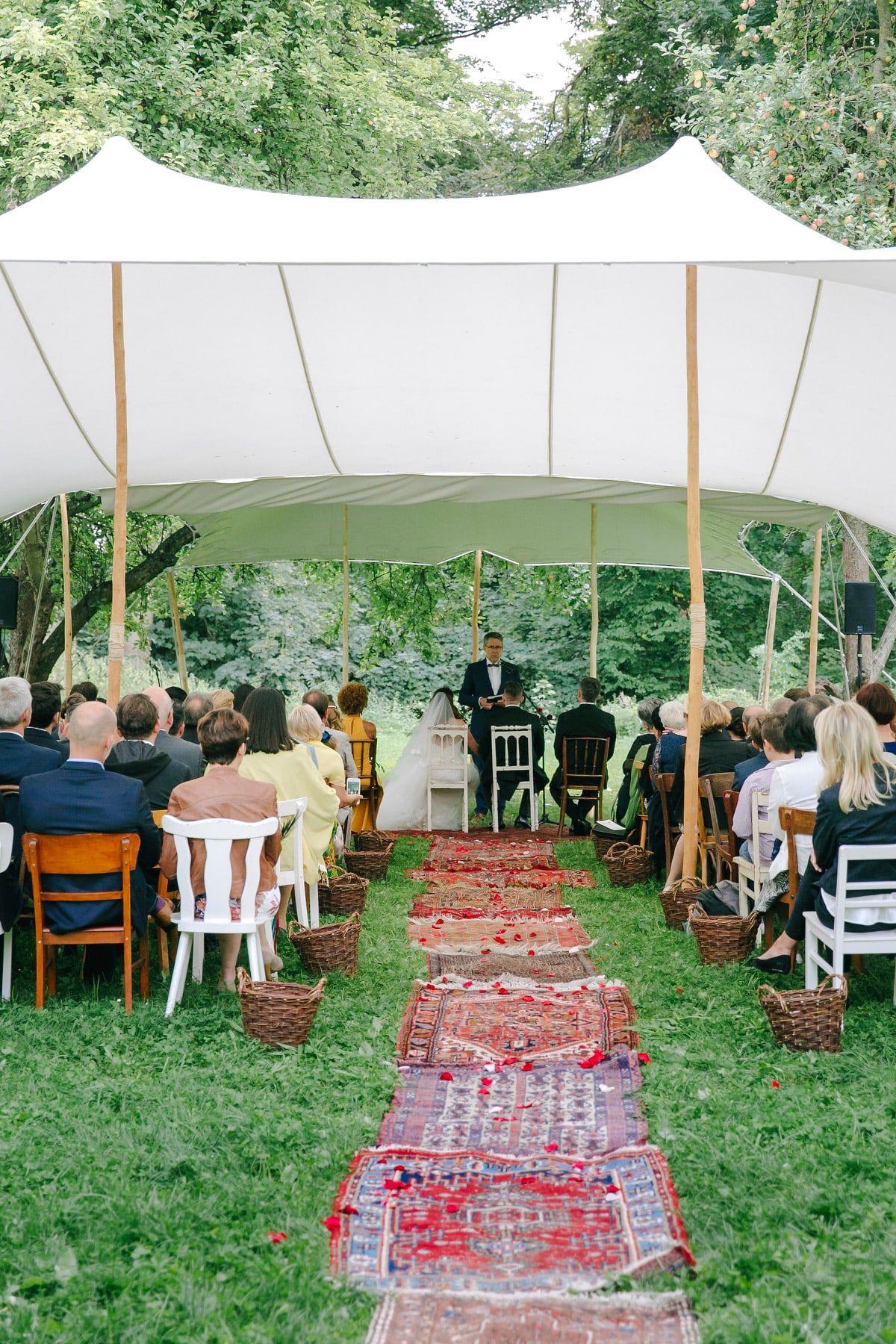 Gartenhochzeit Freie Trauung Im Zelt Hier Wunderschon Auf Dem Rasen Mit Alten Bunten Teppichen Fur Den Weg Zur Zere Gartenhochzeit Trauung Hochzeit Draussen