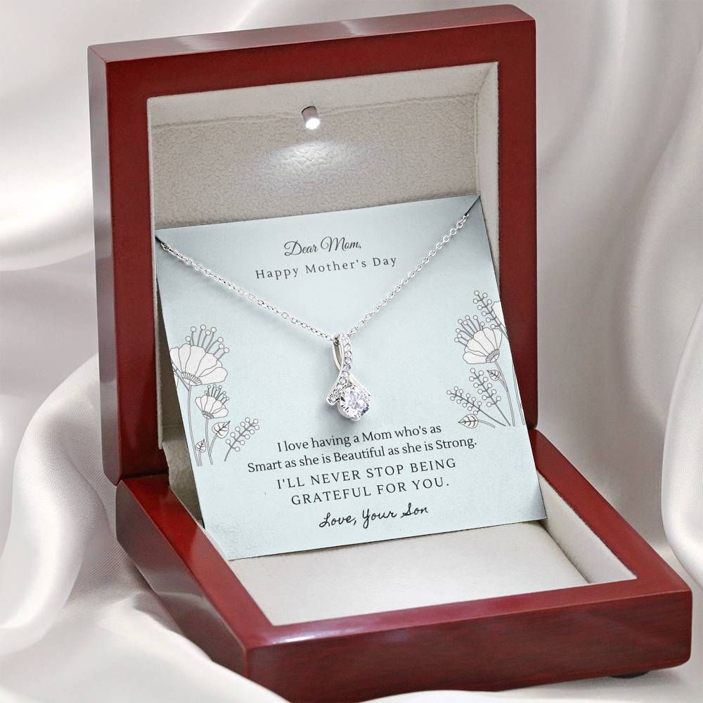 """Dear Mom, Happy Mother's Day. I love having a Mom who's as Smart as she is Beautiful as she is Strong. I'll never stop being grateful for you. Love, Your Son."" Melt her heart with this ALLURING BEAUTY necklace gift! The petite ribbon shaped pendant is finished with 14K white gold over stainless steel, and is embellished with dainty clear crystals surrounded by a sparkling 7mm round cut Cubic Zirconia. The adjustable cable chain allows the necklace to be worn at 18"" to 22"" in length. This neckl"
