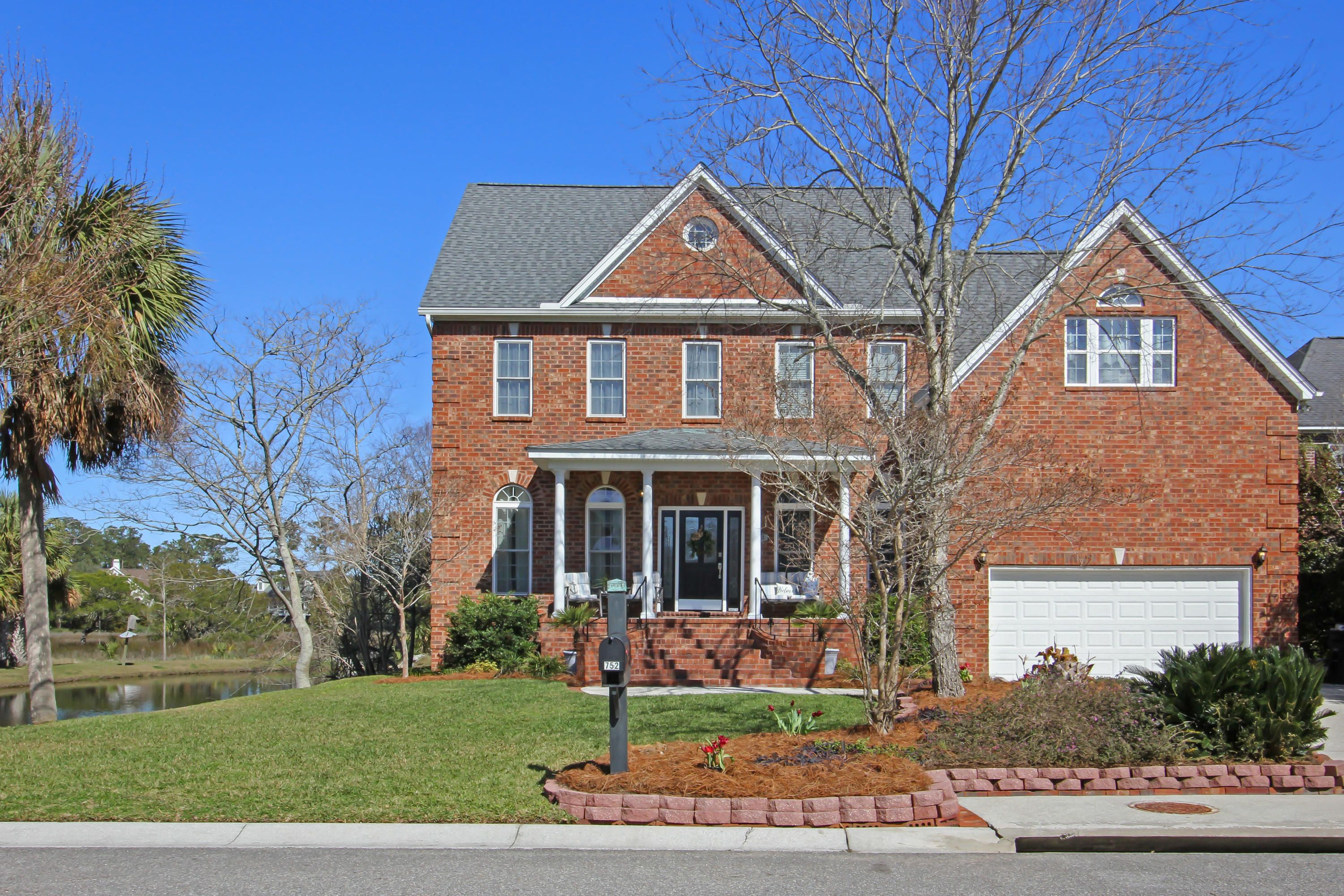 Stately all brick home situated next to a pond with