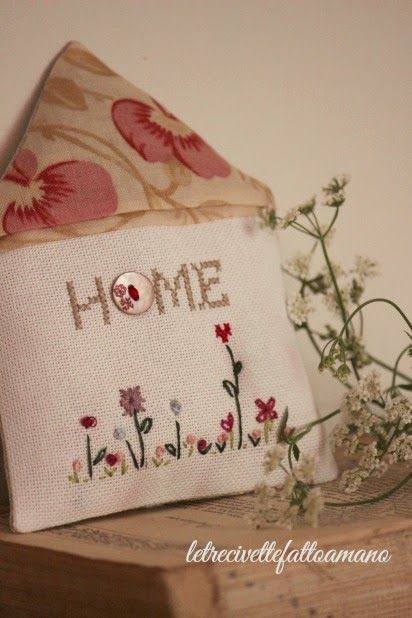 """house shaped pillow with """"Home"""" stitched on it"""