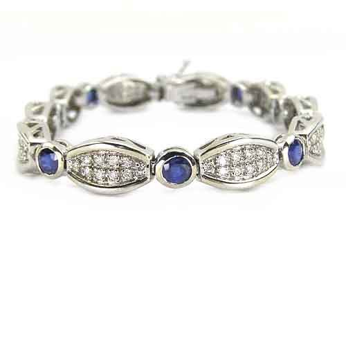 Modern Pave Diamond Bracelet With Blue Sapphire Accents -  This item is available with a 3 week delivery time.  This diamond sapphire bracelet is adorned with a total weight of 5.75cts of sparkling round sapphires and diamonds combined. Beautiful blue sapphires alternate with brilliant diamond-filled lozenge shapes in this contemporary bracelet in 14K white gold. The bezel-set sapphires have open filigree design on the sides of the setting in keeping with the sides of the settings for the...