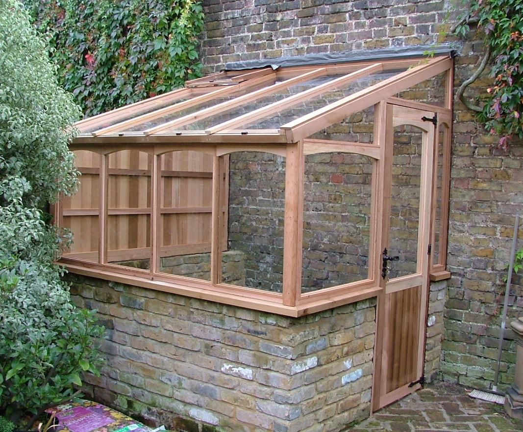 greenhouse built against brick wall for thermal mass