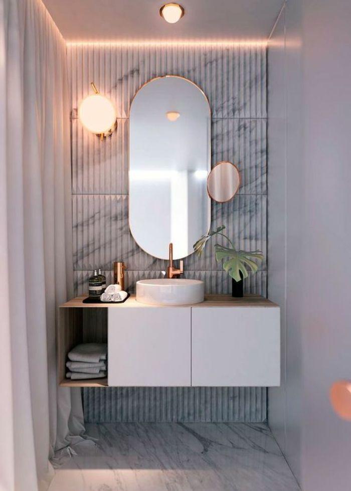 miroir lumineux salle de bain en forme ovale avec un petit miroir rond supplmentaire et un meuble suspendu