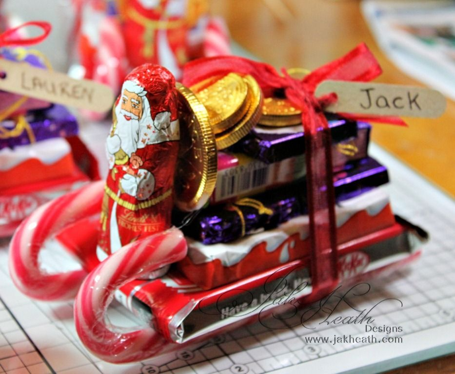 sweet stack made into shape of a sleigh using candy canes for the sled feet and a chocolate santa at the helm - Candy Sleighs For Christmas