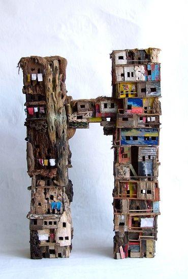 Slum quarters van Eric Cremers | Slum quarters verbeeldt een tweeledig, door een overbrugging verbonden, bouwwerk waarbij een deel volledig uit organische materialen bestaat en het andere uit een variatie van afvalmaterialen.