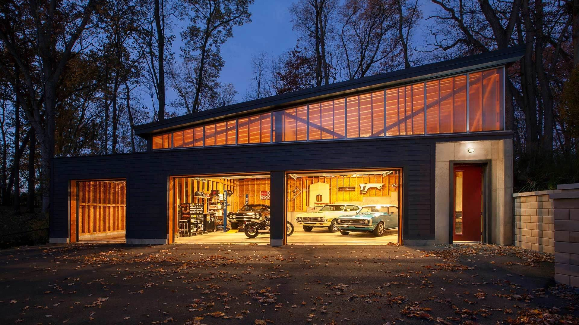 Front View Of Of Auto Garage Workshop At Dawn Features Raised Clerestory Shed Roof That Compliments The Lines Of Pr Modern Garage Garage Design Garage Exterior