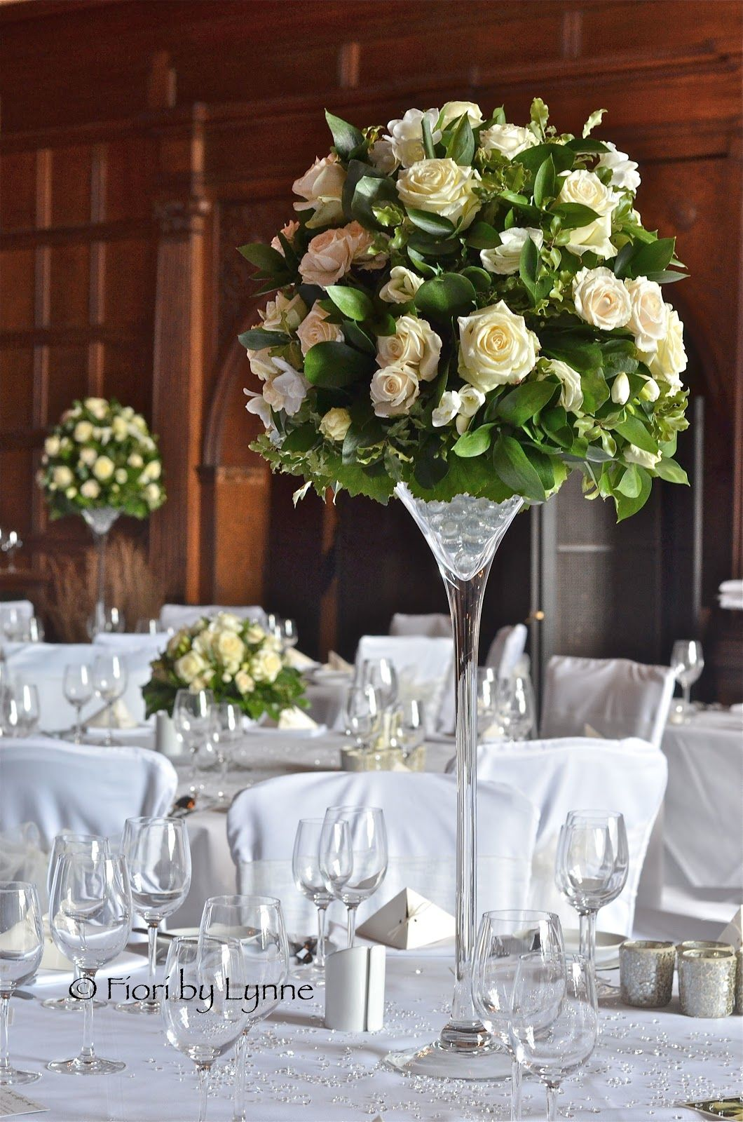 Tall table centres of mixed roses and lisianthus in