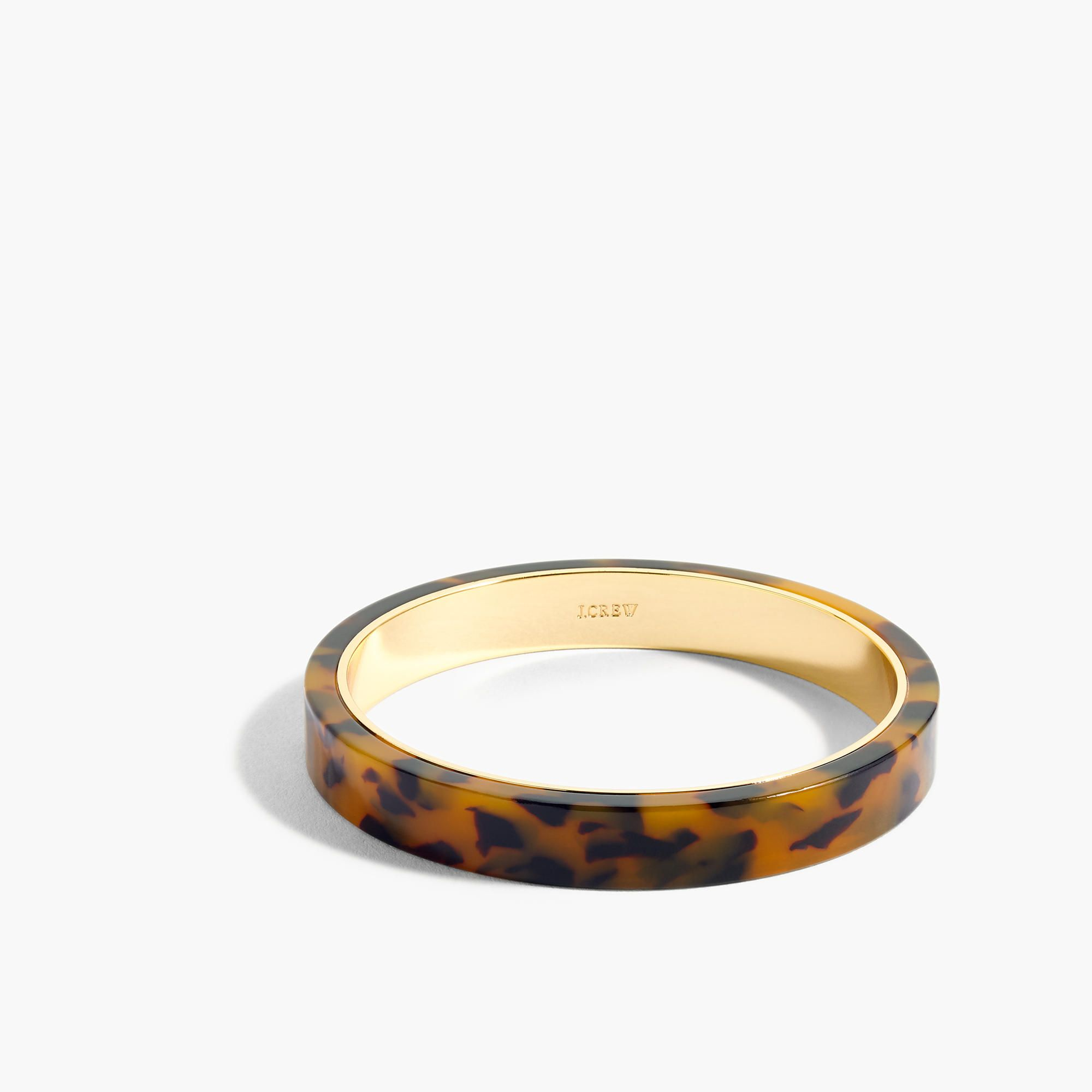 A classic resin bangle that looks good on its own or stacked brass