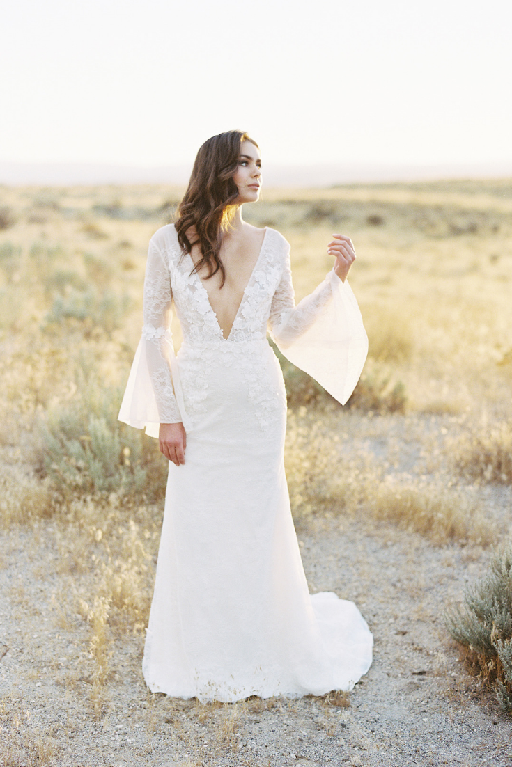 The rosalie wedding gown draws you in with her sheer sleeves a low