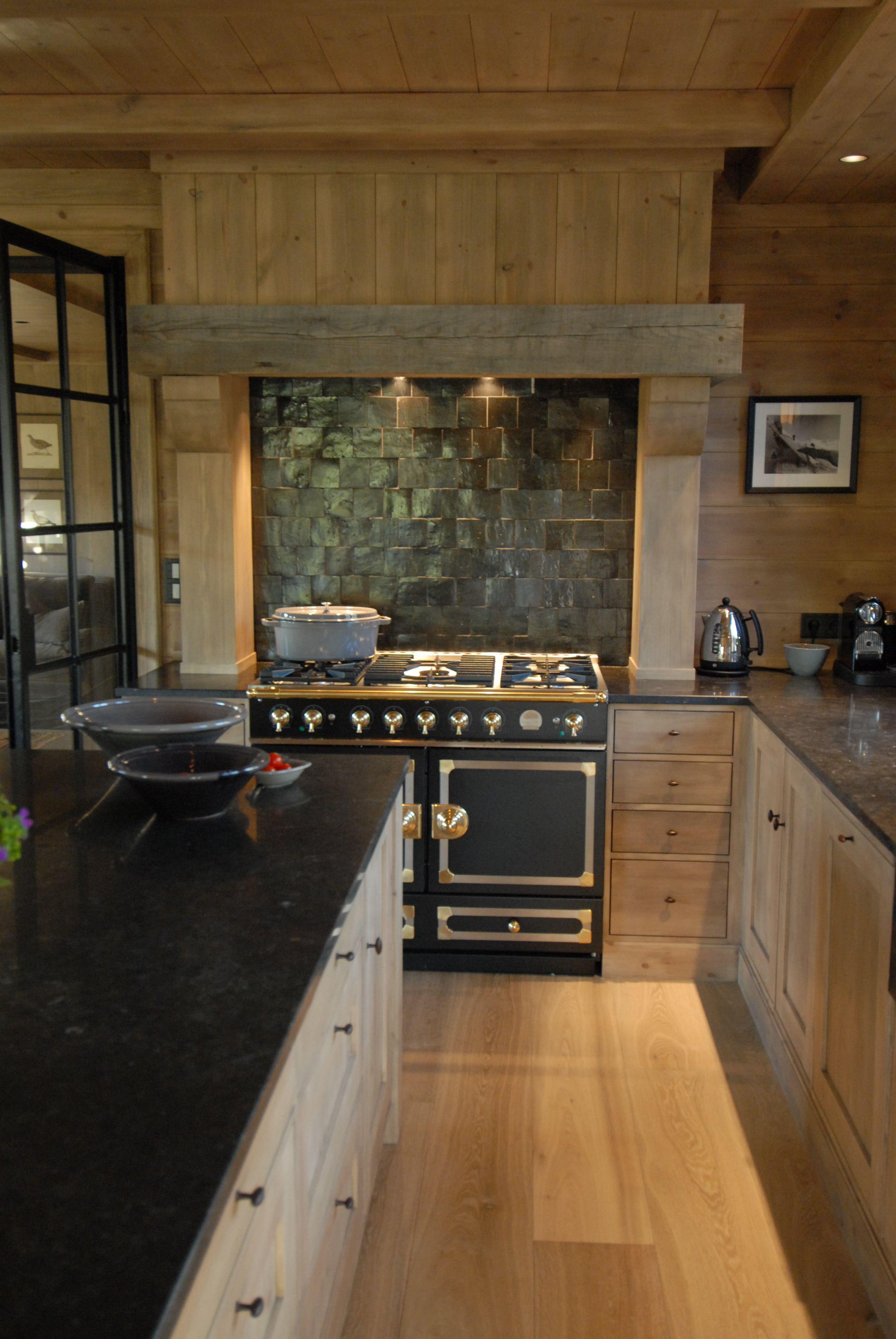 Rustic kitchen in norway with black cornue stove u black tile