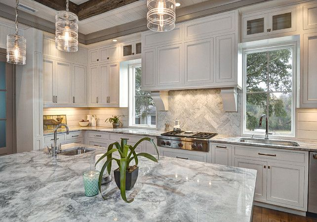 White Kitchen Herringbone Backsplash kitchen. corbels, darker trim, double stack cabinetry, gas range