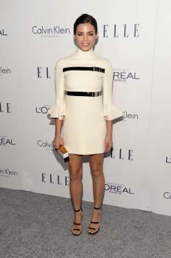 Wore a cream colored bell-sleeved dress and strappy sandals. - Getty