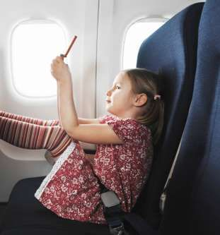 Girl on aeroplane using handheld electronic device. - Henrik Sorensen/Stone Sub/Getty Images