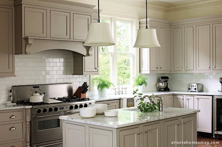 Light warm grey cabinetry, white backsplash tile, hood cabinetry ...
