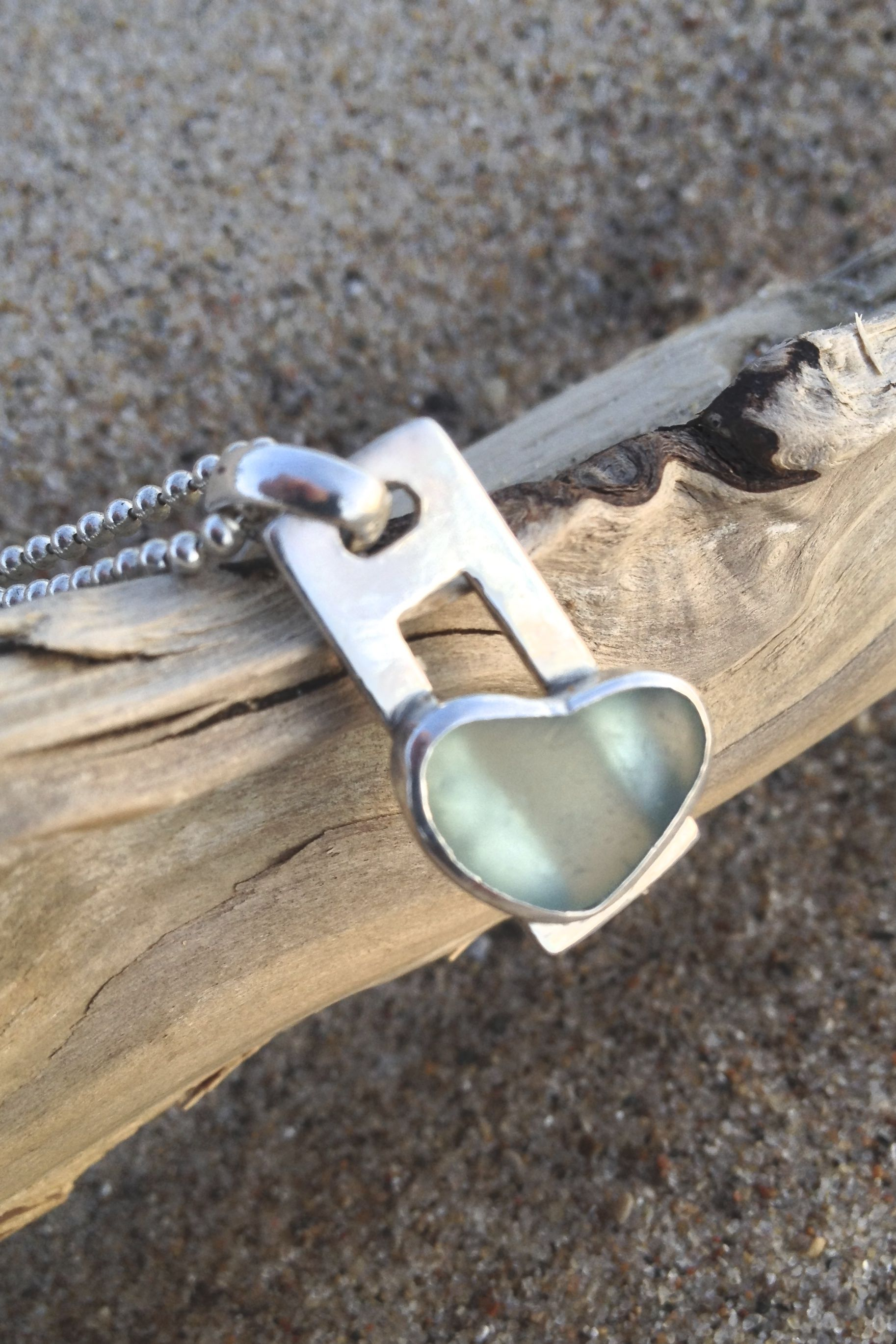 Open back bezel set with fine SS. Unaltered heart shaped e glass soldered to a open rectangle SS pendant, large bail.