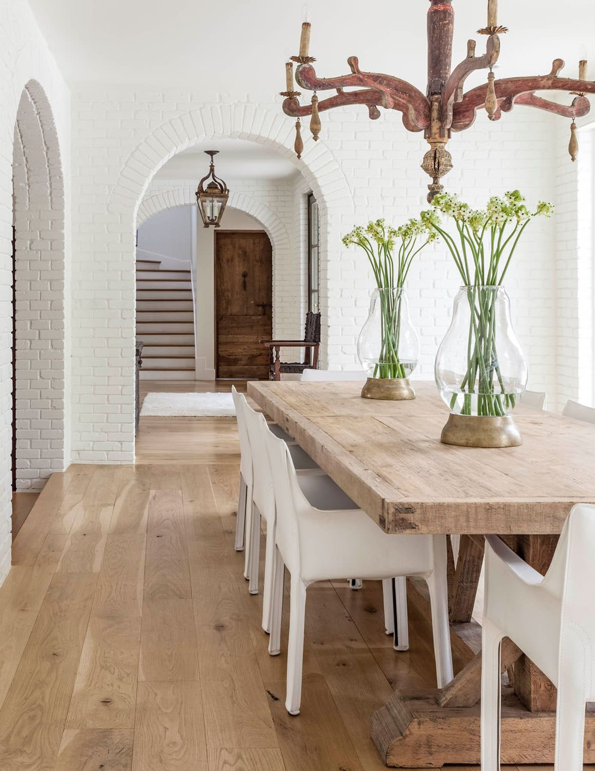 Painted white brick walls interior arches archways wide plank wood floors modern chairs paired with  farmhouse dining table robert also rh pinterest