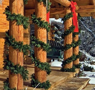 porch columns of a log cabin decorated for christmas with garlands