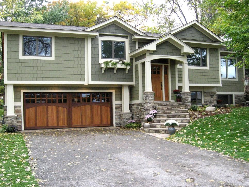 This Lovely Split Level Home Blends In Beautifully With The Trees And Lawn Around It Thanks To Its Soft G House Exterior House Paint Exterior Exterior Remodel