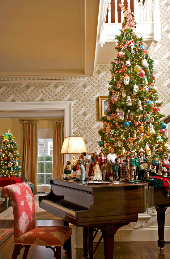 Figurines Of Carolers Gather On The Piano Around Christmas Tree In This Perfectly Joyful Foyer