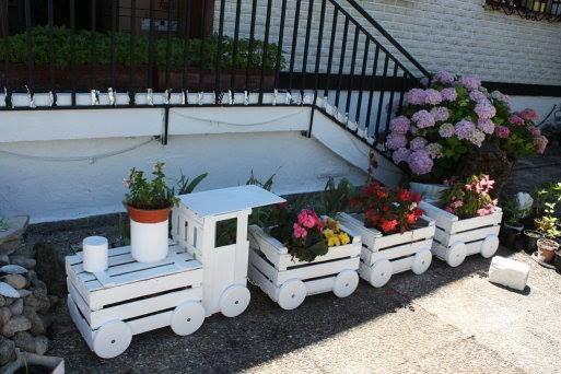 Blumenzug aus Holzkisten mit Baumscheiben Holztellern und als Schornstein eine Dose siehe 2