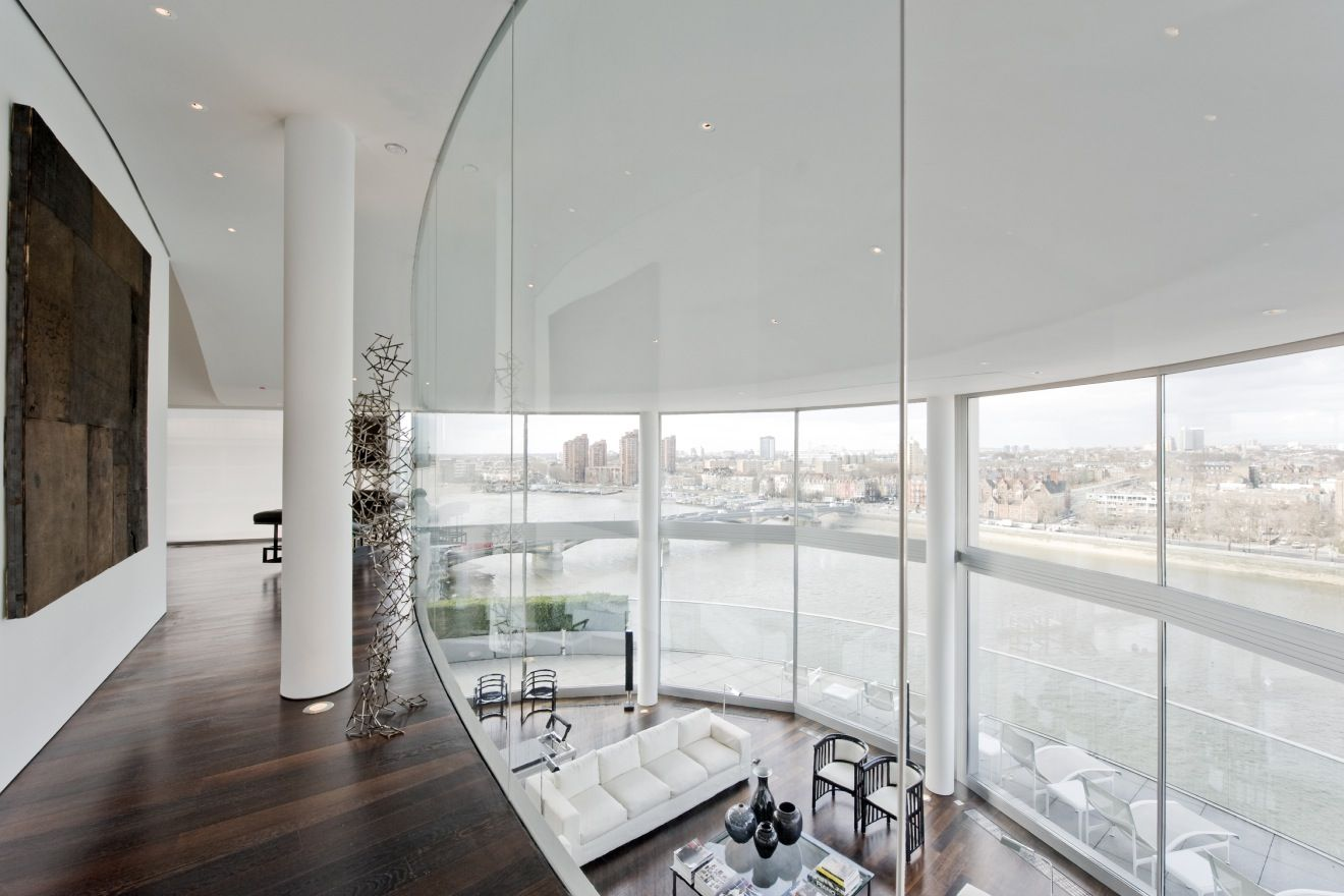 A glass staircase leads up to a sprawling, glass walled mezzanine level  that overlooks both