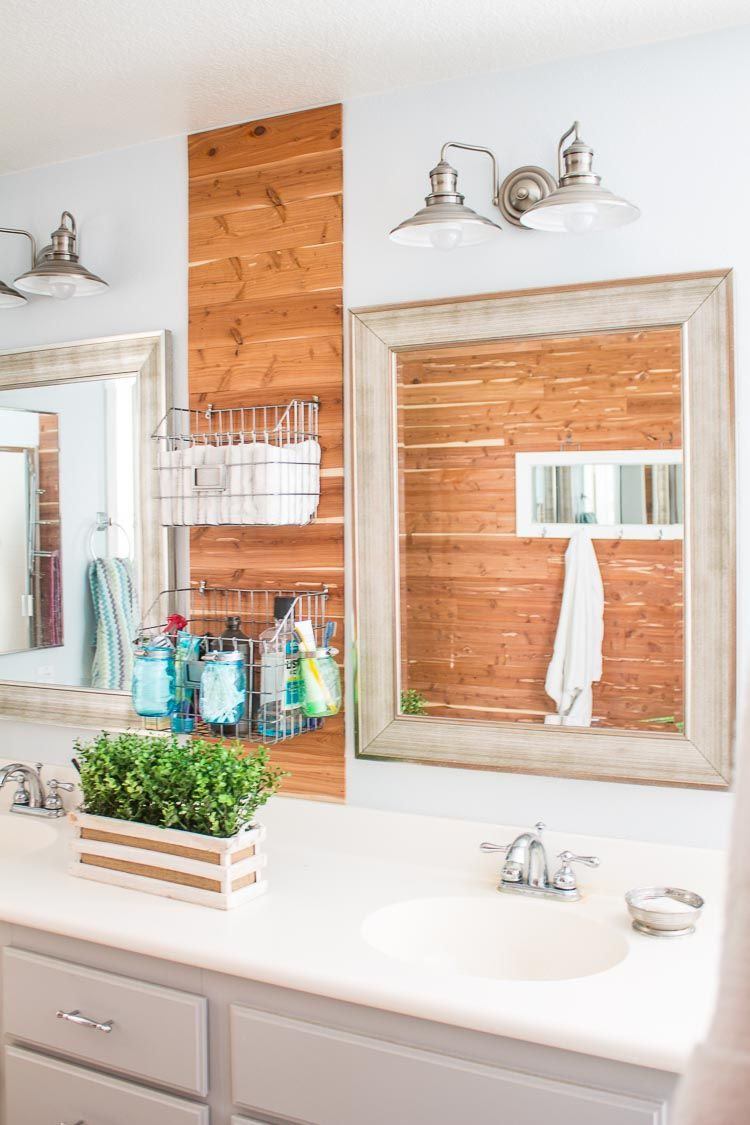 DIY Rustic Industrial Master Bathroom Update with a cedar wall, new lighting, mirrors, baskets and more. Get a gorgeous rustic farmhouse look.