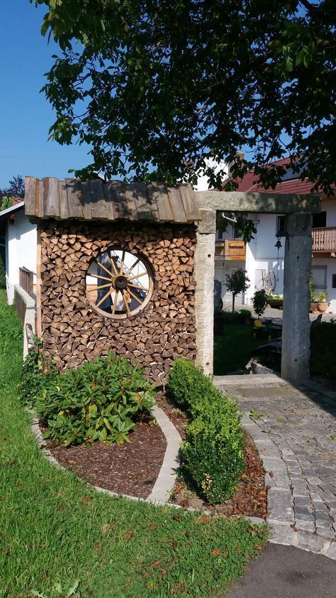 Photo of Pile of wood with wagon wheel as privacy screen – Marion Griener – garden decor