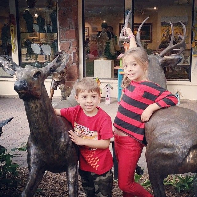 Kids post for a picture with the brass deer.,