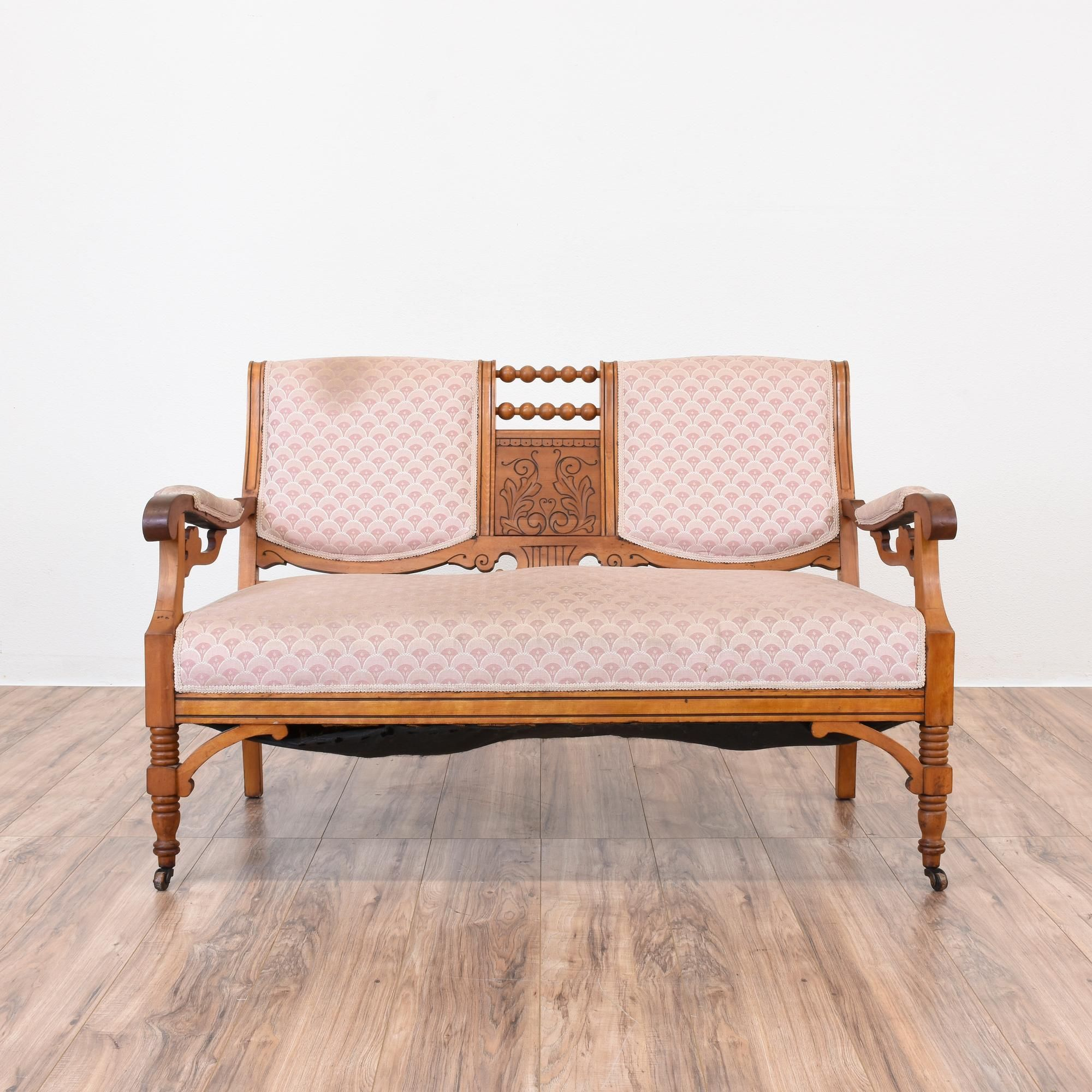 This antique eastlake settee is featured in a solid wood with a