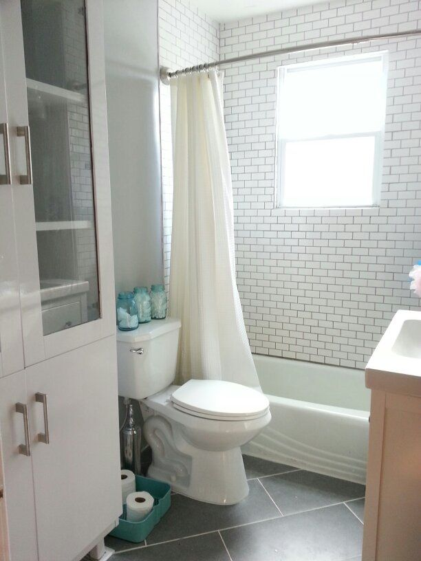 White Bathroom. White subway tile. Large gray floor tiles ...