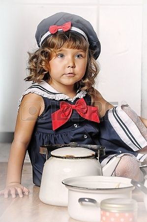 little girl in the kitchen of cookware