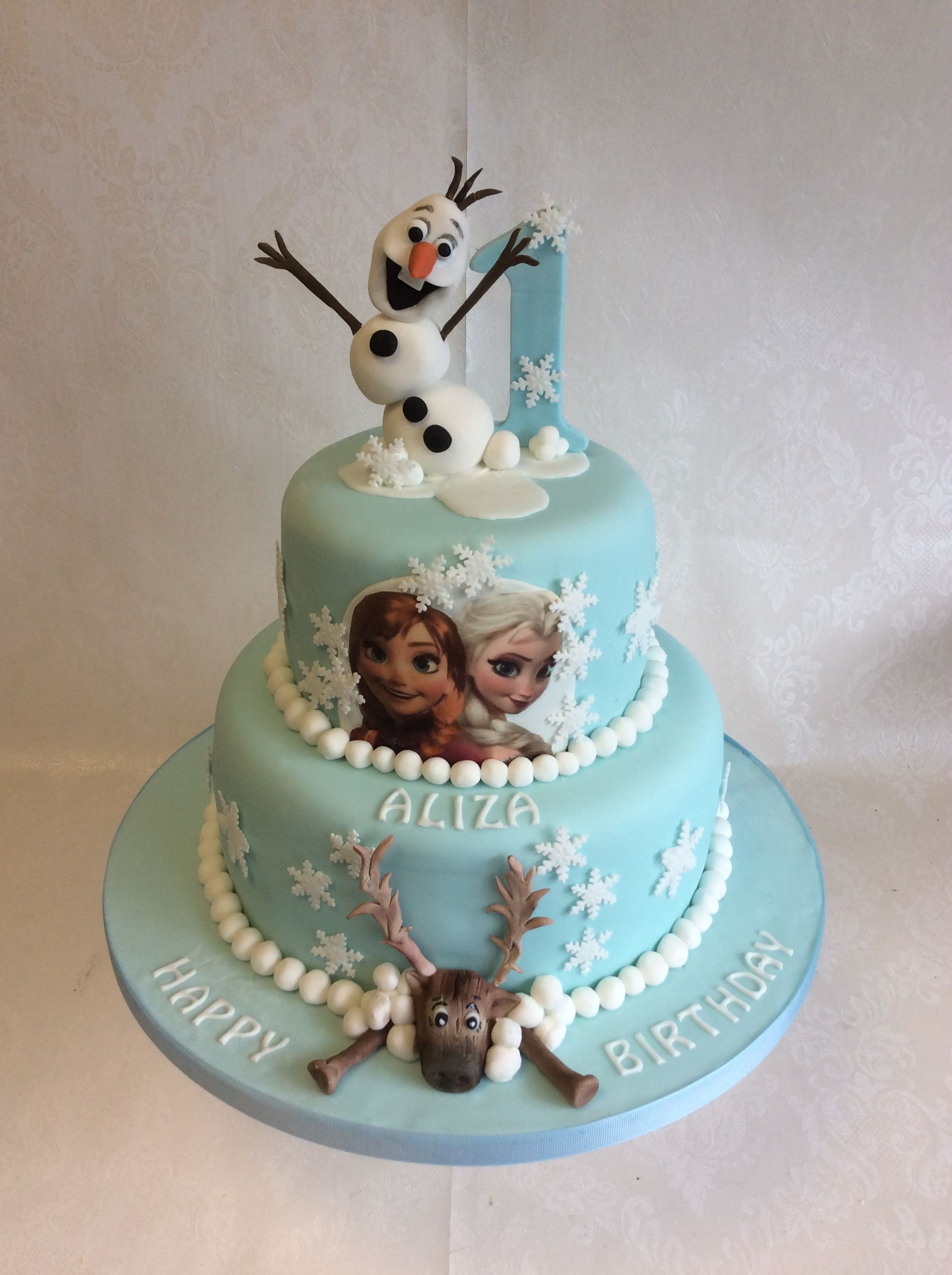 2 tier cake with handmade Olaf and Sven characters plus Elsa and Ana