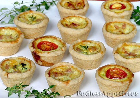 Mini quiches made with egg, two cheeses, diced green onions and diced ham, in a flaky homemade pastry crust, topped with sliced cherry tomatoes and fresh herbs.