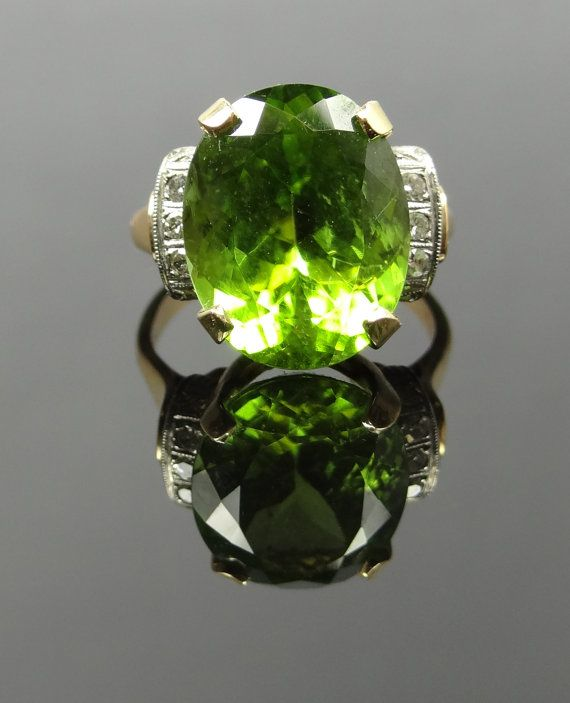 This stunning 40's era ring has an amazing combination of two tone gold, and simple styling that really creates a great stage for the gorgeous Peridot center. The stone is super fine quality Peridot, with great faceting and a rich lime green color that really pops! The yellow gold really brings out the warm yellow undertones of the stone, while the band of white gold really accents the whiteness of the diamond shoulders!