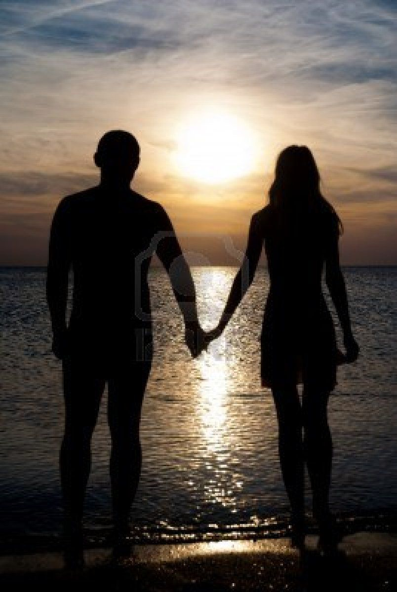 young couple silhouette on a sea beach holding hands and looking
