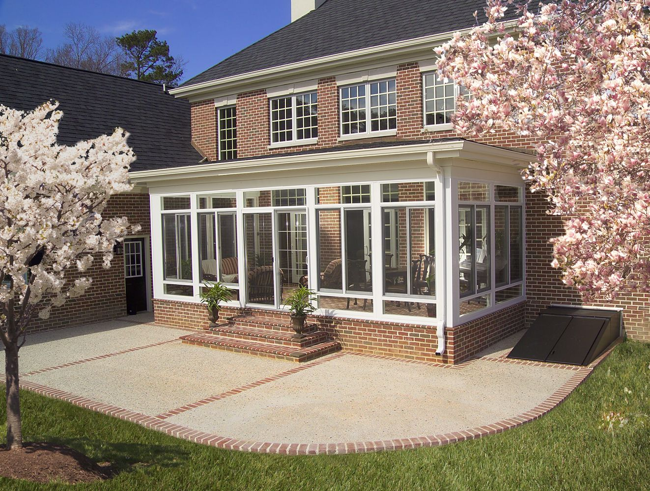Enclosed porch outside view many people use sunrooms to for Back patio porch designs