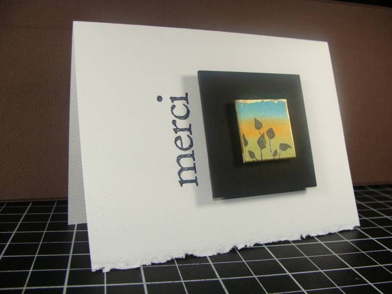 handmade card ... clean and simple ... inchie framed as a piece of art ... large black square as frame ... inchie bordered in gold ... MERCI as only script ... luv it!!