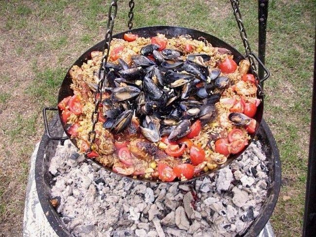 paella sur le barbecue à feu de bois. (paella-auf-dem-schwenkgrill