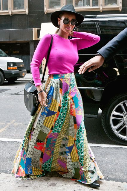 Beyonce spotted wearing long patchwork skirt and neon pink blouse with black accessories.