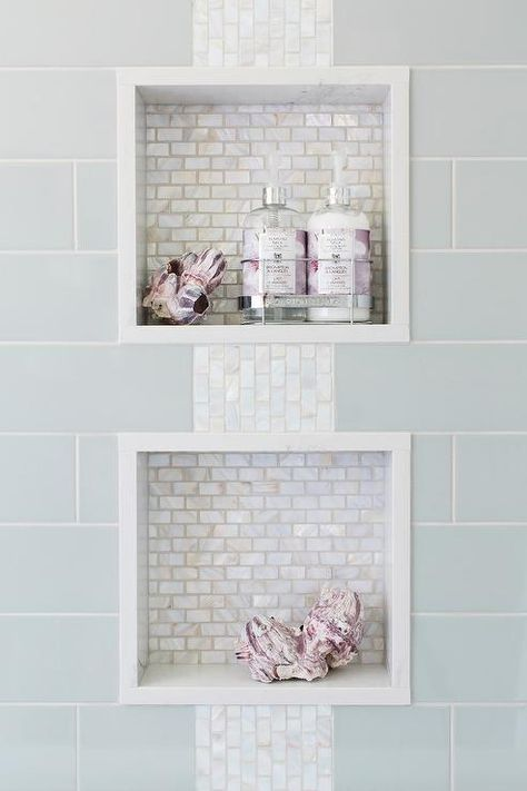 Blue subway shower tiles frame two white glass mini brick tiled niches connected by iridescent accent also