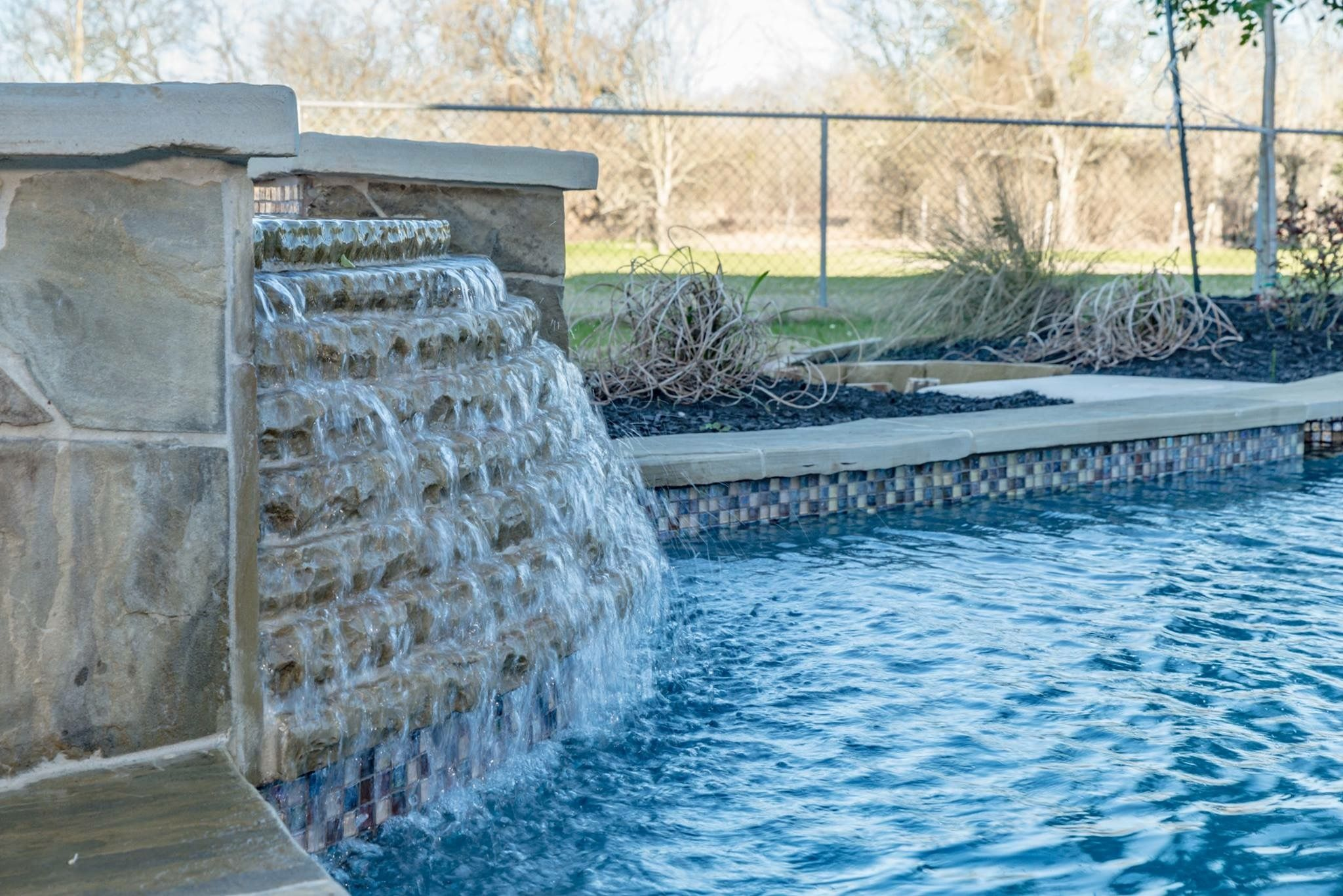 This pool has flagstone decking, glass tiles for the water line tile ...
