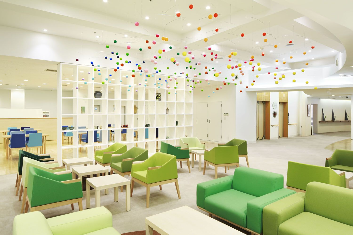 2_emmanuelle_moureaux_shinjuen.jpg - In the lounge area, colorful bubbles are dancing in the air above chairs and sofas colored in shades of green, which give image of green grass and soap bubbles floating in the park on sunny days.