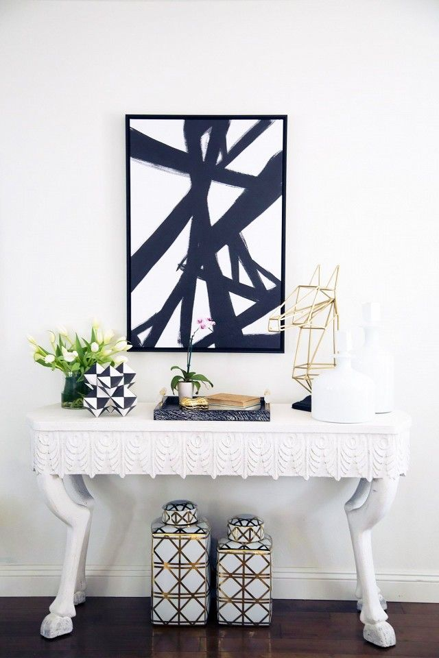 Space with an eclectic white table, styled with monochromatic and gold accessories