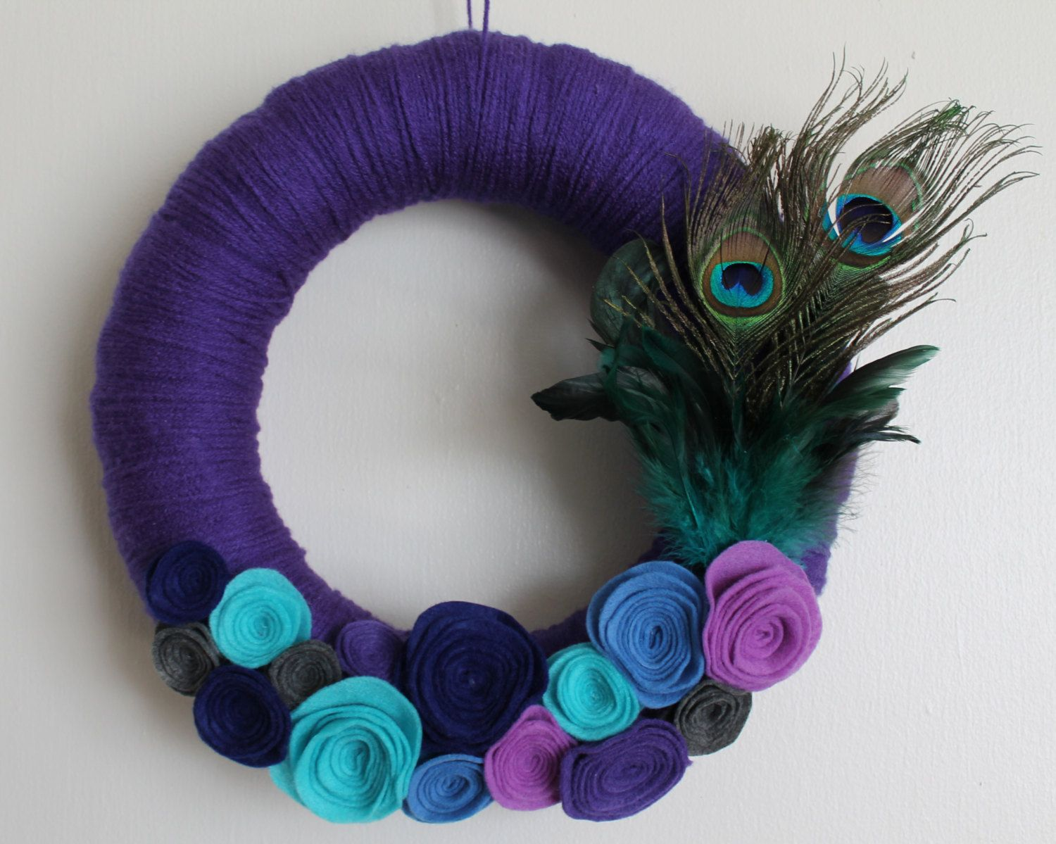 12 inch yarn wreath with peacock feathers and handmade rosettes. via Etsy.